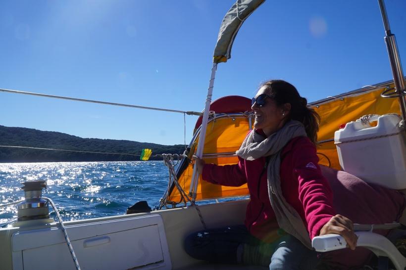 Woman helming a sail yacht